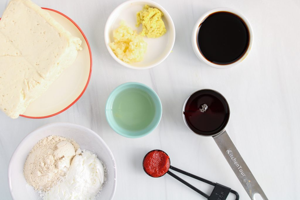 Showing are the ingredients needed to make this recipe: maple syrup, soy sauce, ginger, garlic, soy product, flour, cornstarch, rice vinegar and tomato paste.