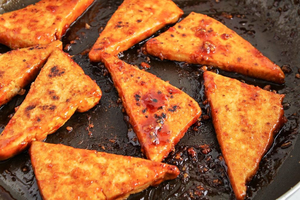 In process picture: there are triangle shape tofu that are cooking in a sweet sauce in a large non stick pan.