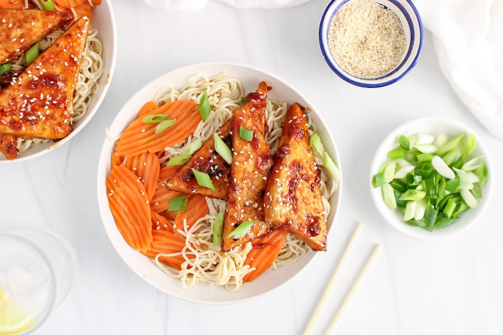 Overhead view on a sticky tofu that's topping a bowl filled with rice noodle and steamed carrots. The tofu is also garnished with white sesame seeds and chopped green onion. There are small bowls on the table containing more sesame seeds and chopped green onions as well as chop sticks and a glass of water with lemon wedges.