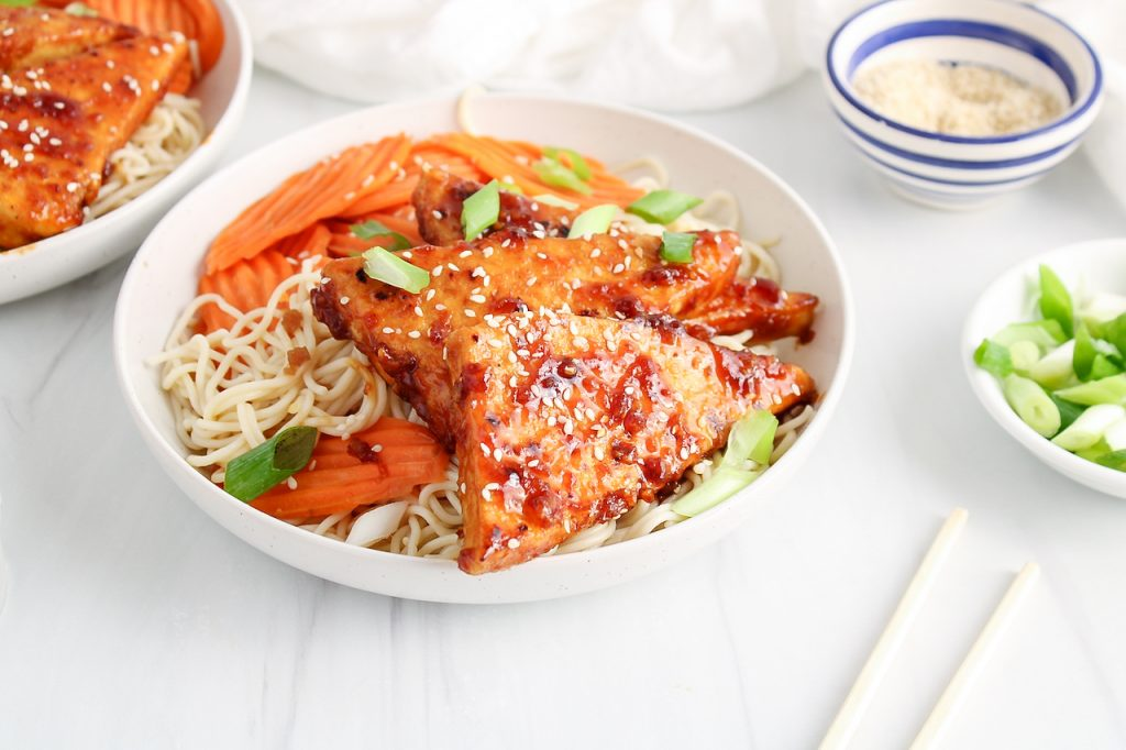 Front angle view on a bowl filled with rice noodles, a sticky tofu, steamed carrots, sesame seeds and green onion. You can see a second bowl with the sticky tofu in the background as well as small bowls with sesame seeds, green onion and chop sticks.