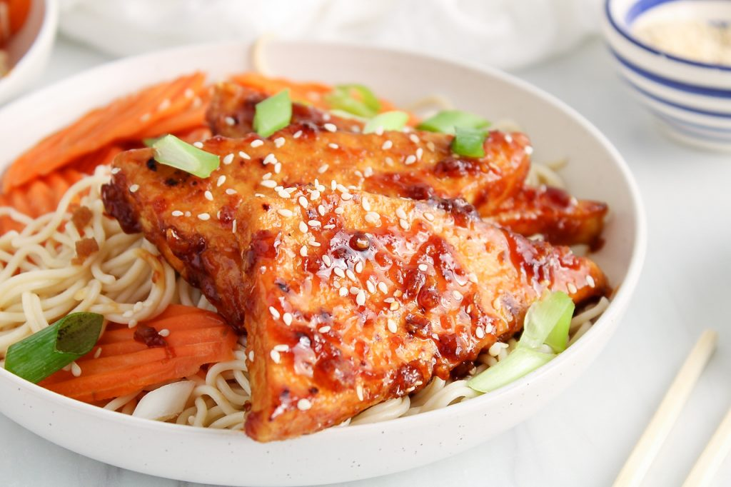 Front angle view on a bowl filled with rice noodles, a sticky tofu, steamed carrots, sesame seeds and green onion. There is a small bowl with sesame seeds in the background and chop sticks on the side. There is a close up on the front piece of sticky tofu to show the texture of the sauce.