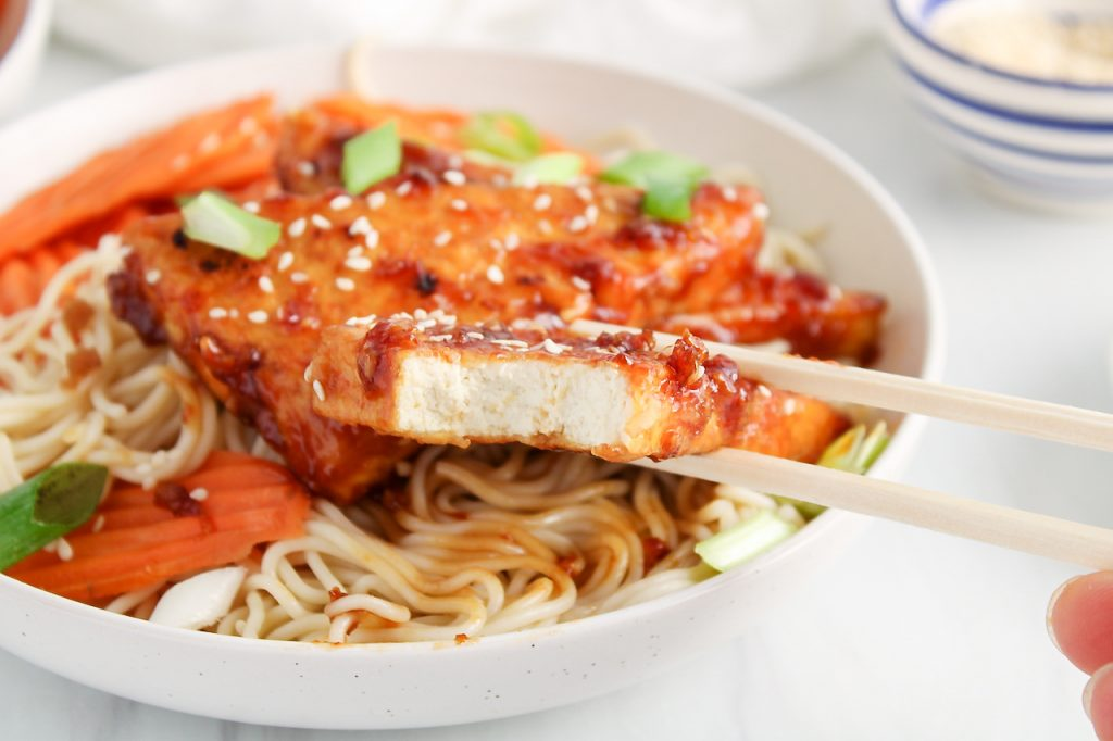 Front angle view on a bowl filled with rice noodles, a sticky tofu, steamed carrots, sesame seeds and green onion. There is a small bowl with sesame seeds in the background. There is a close up on the front piece of sticky tofu (hold by chop sticks) that has a bite taken off to show the texture of the sauce and the middle part of the tofu.