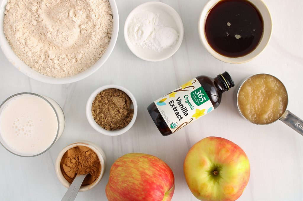 Showing are the ingredients needed to make this recipe: fruits, flour, vegan milk, maple syrup, spiced, vanilla extract, flax seeds, baking powder, baking soda and fruit purée.
