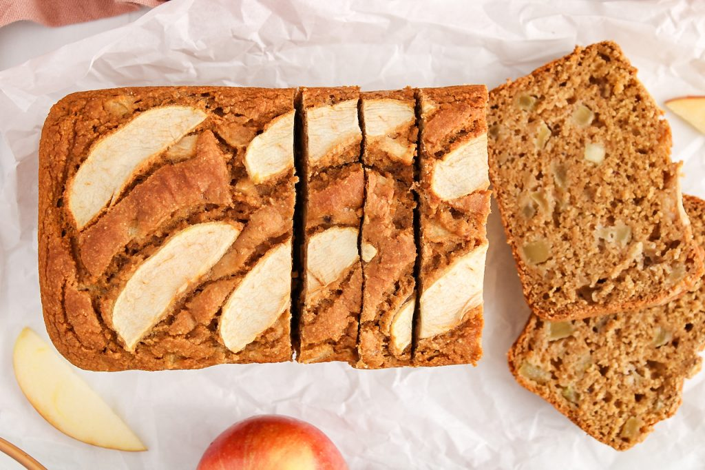 Overhead view on a vegan apple cinnamon bread. The loaf is topped with sliced apples and the bread is half sliced. There are fresh apples around the loaf as well as a pink hand towel and sliced apples.
