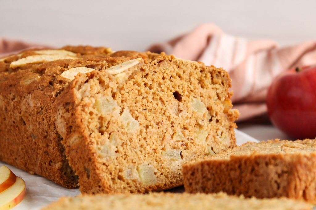 Front view on a half sliced vegan apple cinnamon bread. There are fresh apples, sliced apples and a pink hand towel in the background. The focus is on one of the slices of apple bread to show the texture and you can see all the diced apple within the slice.