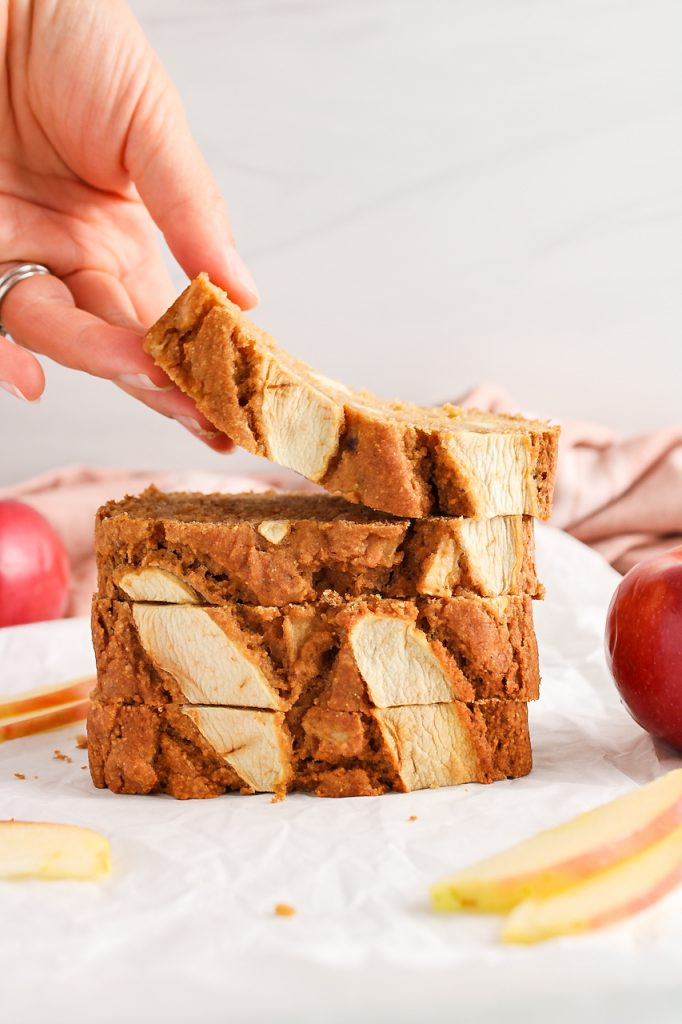 Front view on a few slices of vegan apple cinnamon bread that are piled on top of each other. You can see a hand that's grabbing the top slice and there are fresh apples in the background.