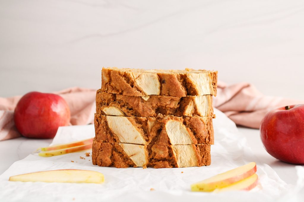 Front view on a few slices of vegan apple cinnamon bread that are piled on top of each other. There are fresh apples in the background as well as a pink hand towel.