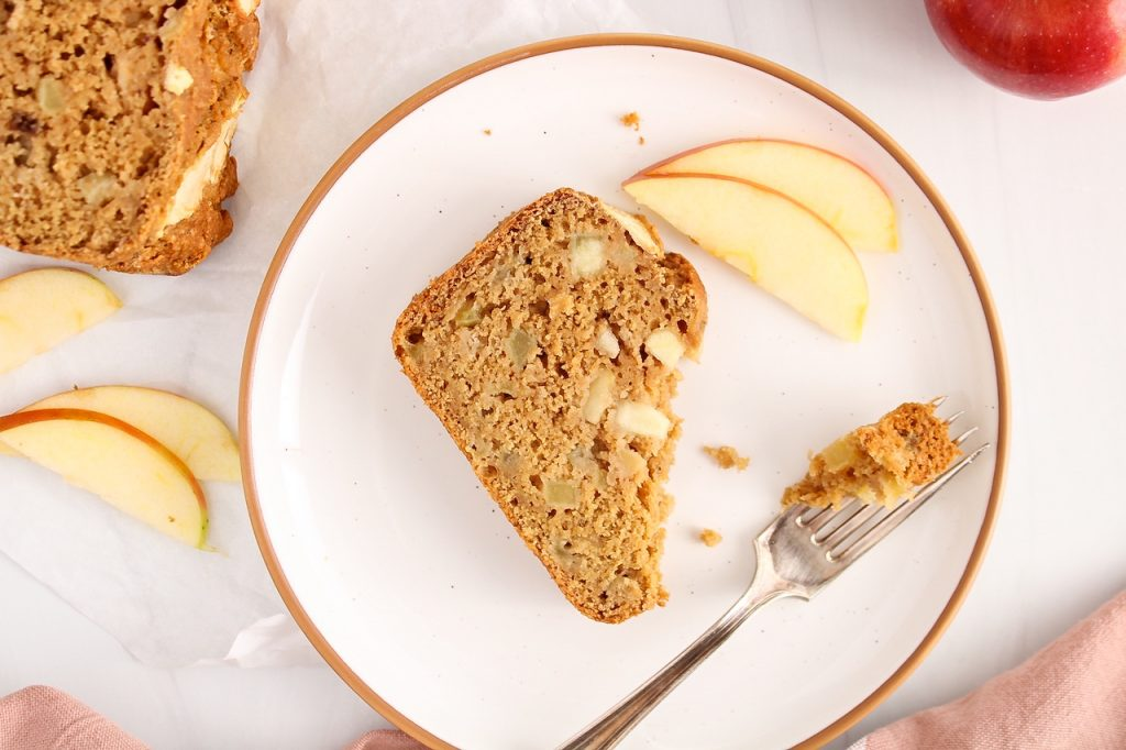 Overhead view on a slice of vegan apple cinnamon bread that has a bite taken off. The slice is on a plate and there is a fork on the side as well as slices of fresh apples.