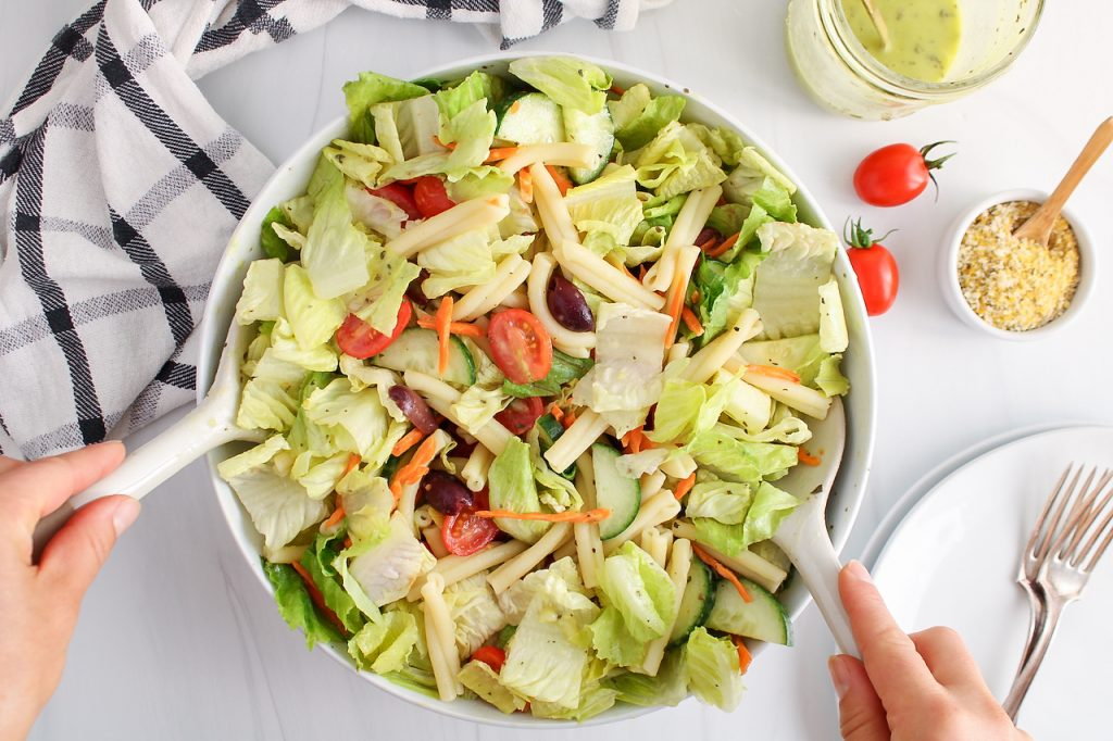 Overhead view on a lartge shallow bowl filled with a salad made with romaine, olives, cherry tomatoes, carrots and cucumber. There is a jar with some more of the dressing beside the salad bowl, plates for serving and a small container containing vegan parmesan.