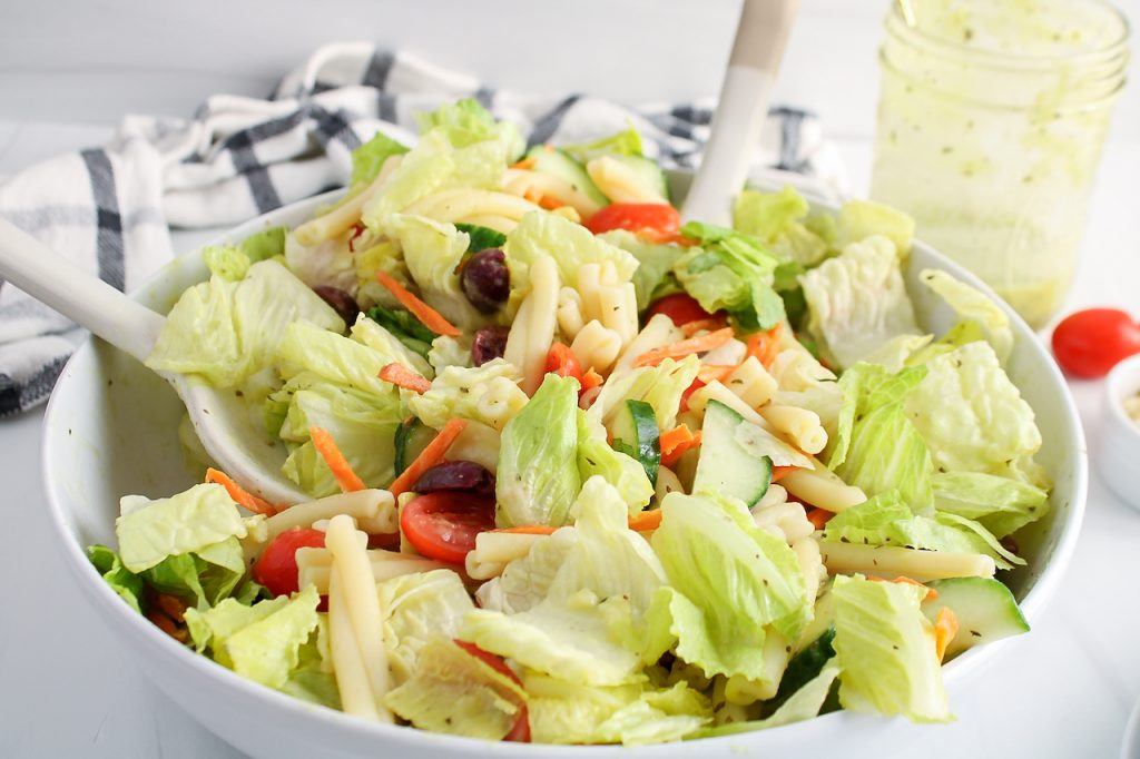 Front angle view on a bowl with a large salad that was tossed in a homemade vegan Italian dressing. There are 2 mixing spoons in the salad bowl and you can see in the background the jar containing some of the dressing, cherry tomatoes and a black and white hand towel.