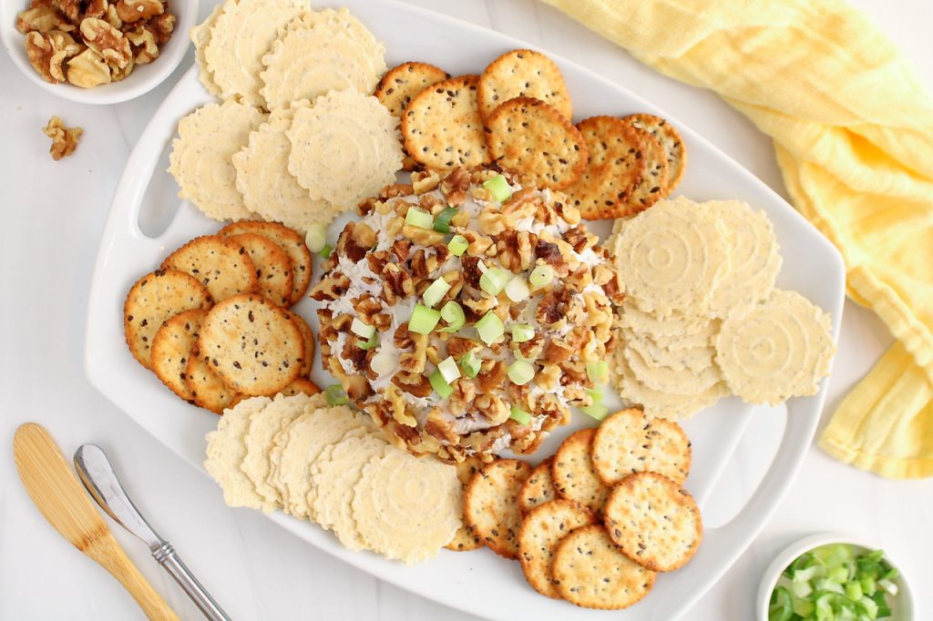 Overhead view on a vegan Hawaiian Cheese Ball that's placed on a large rectangular white plate and surrounded by crackers. The cheese ball is garnished with chopped walnut and green onions. Also on the side, there are 2 cheese knives, more green onions and a yellow hand towel.