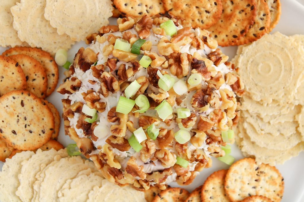 Close up on a vegan hawaiian cheese ball. The ball is covered with walnuts and garnished with green onions. There are crackers surrounding the cheese ball as well.