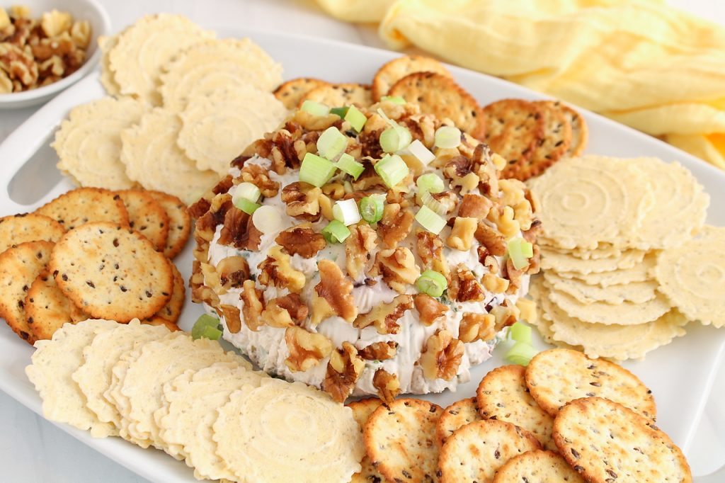 Front angle view on a vegan Hawaiian cheese ball that's garnished with chopped walnuts and green onion. The cheese ball is also surrounded by crackers.