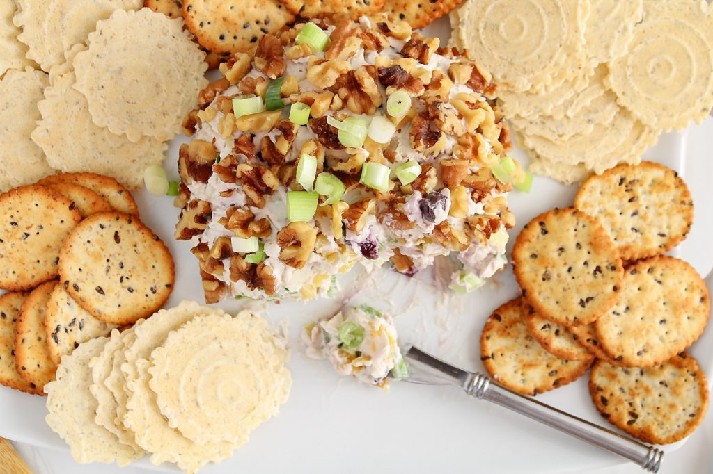 Overhead view on a vegan Hawaiian cheese ball that has a few bites taken off and is placed on a large rectangular serving plate. There are crackers surrounding the cheese ball and also a cheese knive with some of the dip over.