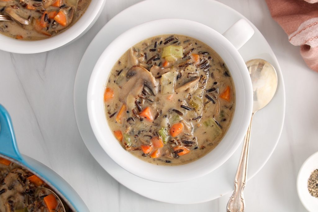 Overhead view on a white bowl placed on a plate and filled with a vegan wild rice mushroom soup. There is a second bowl on the side as well as the large pot used to cook the soup, a pink hand towel and black pepper in a small white bowl.