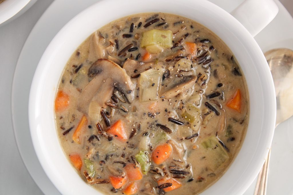 Close up on an overhead view on a bowl of vegan wild mushroom soup. There is a spoon on the side of the bowl as well as black pepper topping the soup.