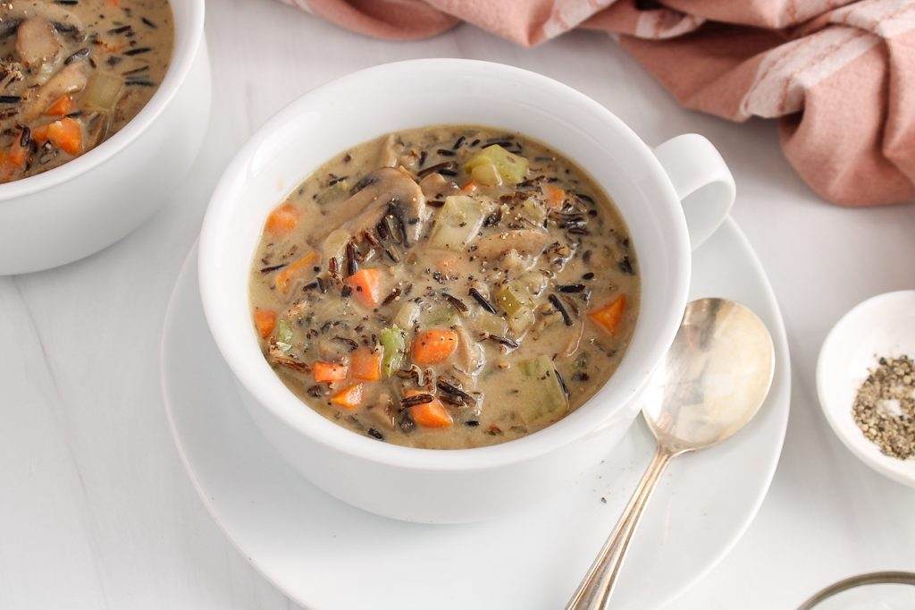 Front angle view on a white bowl containing a healthy vegan wild rice mushroom soup. The soup is garnished with black pepper and there is a spoon on the side of the bowl as well as a pink hand towel in the background.