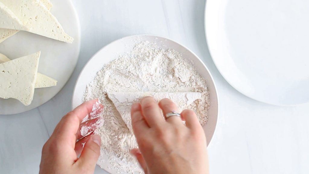 In process picture: you can see 2 hands that are breading slices of tofu in a flour mixture