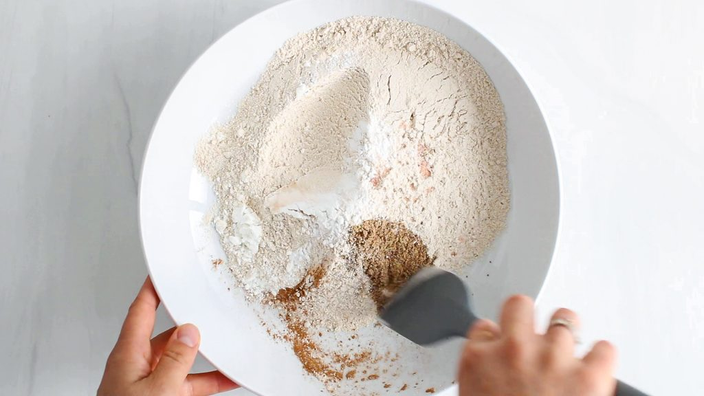 In process picture: there is a dry mixture being mixed in a bowl with a spatula.