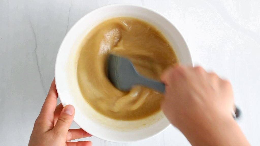 In process picture: there is a brown liquid being mixed in a bowl with a spatula.