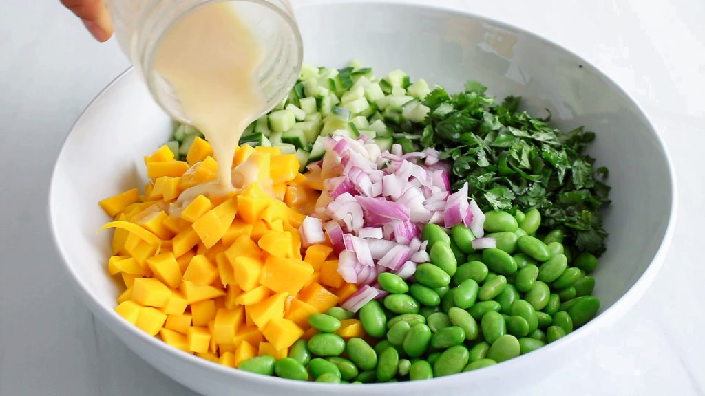 In process picture: you can see a hand holding on a small jar that's pouring a dressing over a bowl with chopped produce.