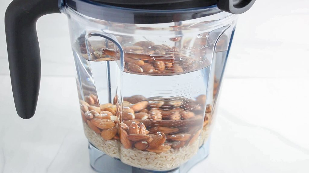 In process picture: showing is a blender that's filled with water, brown rice and raw almonds.