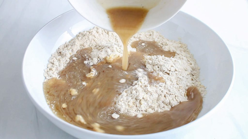In process picture: there is a wet brown mixture that's being poured over a mixture of rolled oats and flour.