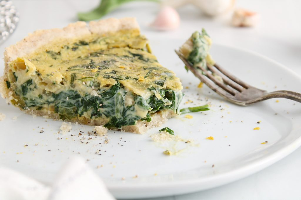 Front view on a slice of vegan spinach quiche that's on a plate with a bite taken off. There is a fork on the plate in the background.