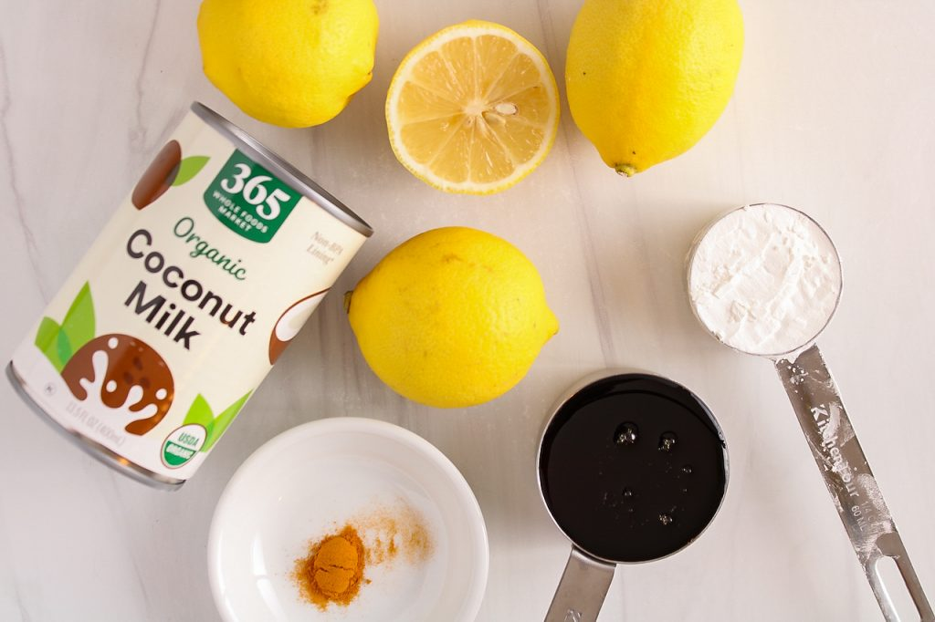 Showing are the ingredients needed to make this recipe: lemon, coconut milk, turmeric, maple syrup and cornstarch.