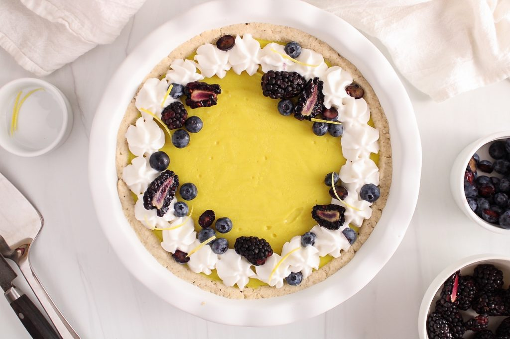 Overhead view on a vegan lemon pie that's decorated with coconut whipped cream and fresh berries. There are more berries in small bowls beside the tart and a white hand towel.