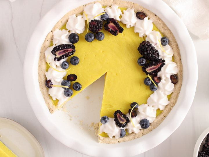 Overhead view on a vegan lemon pie garnished with whipped cream and berries. There is a slice of pie that was taken off.