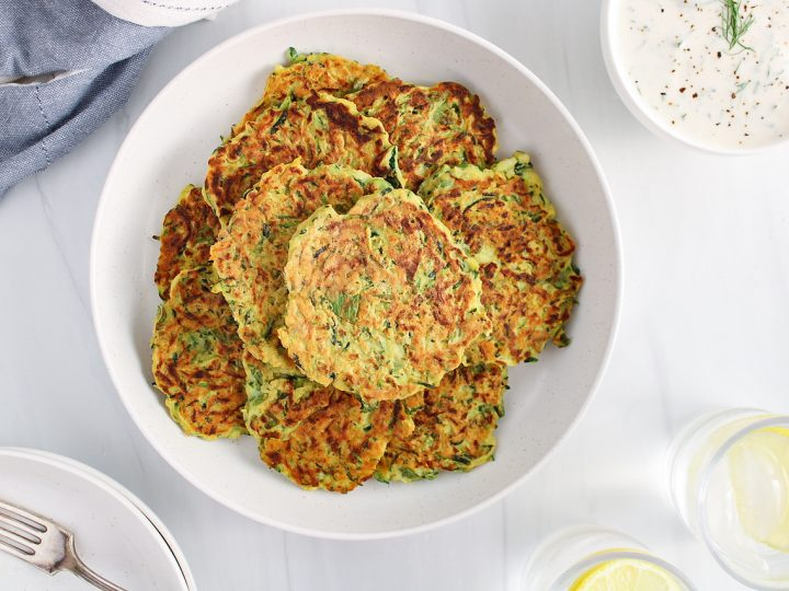 Overhead view on a pile of vegan zucchini basil fritters placed on a white plate. There are glasses of water beside the plate, a blue hand towel and a small bowl with a white sauce.