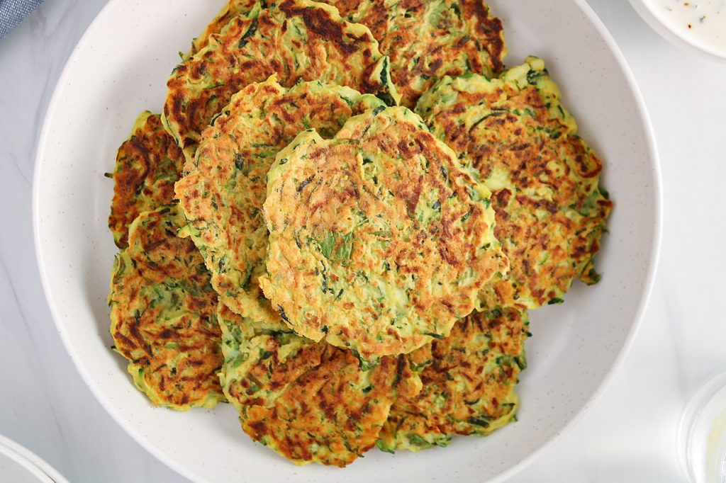 Overhead view on a pile of vegan zucchini basil fritters placed on a white plate. There is a focus on the top fritter.