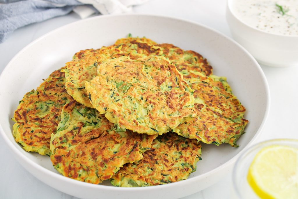 Front angle view on a few vegan zucchini basil fritters placed on a white plates with a bowl containing a white sauce in the background.