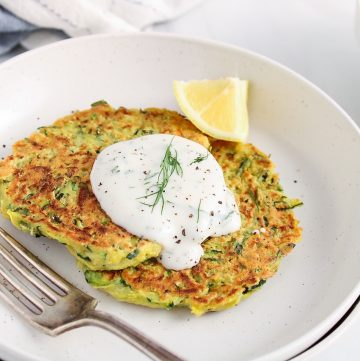 Front angle view on 2 vegan zucchini basil fritters placed on a small plate and garnished with a vegan dill yogurt sauce. There is a lemon wedge on the side and the fritters are garnished with ground black peppers.