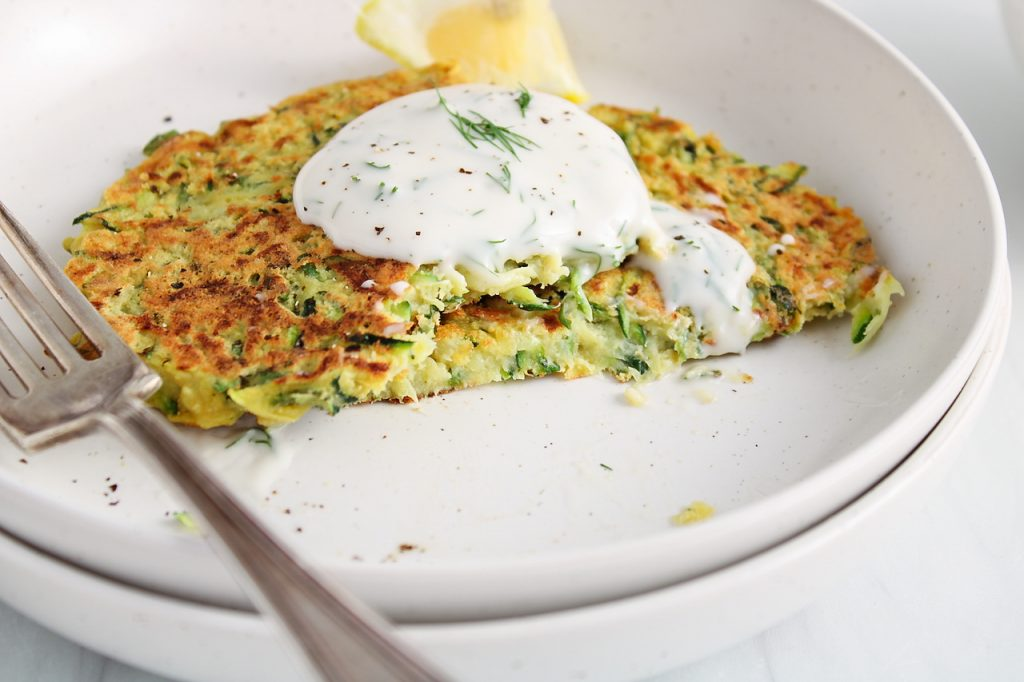 Close up front view on a few zucchini basil fritters placed on a plate and garnished with a simple dill yogurt sauce. There is a fork on the place and the fritters are garnished with ground black pepper.
