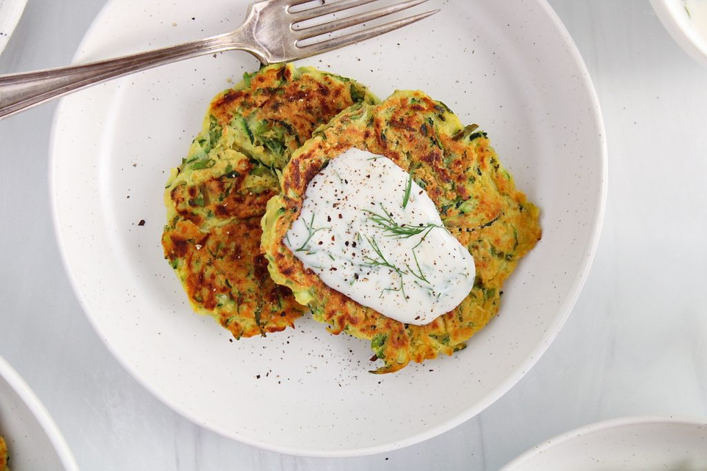 Overhead view on 2 vegan zucchini basil fritters placed on a plate and garnished with a dill vegan yogurt sauce, fresh dill and ground black pepper. There is a fork on the side of the plate as well.