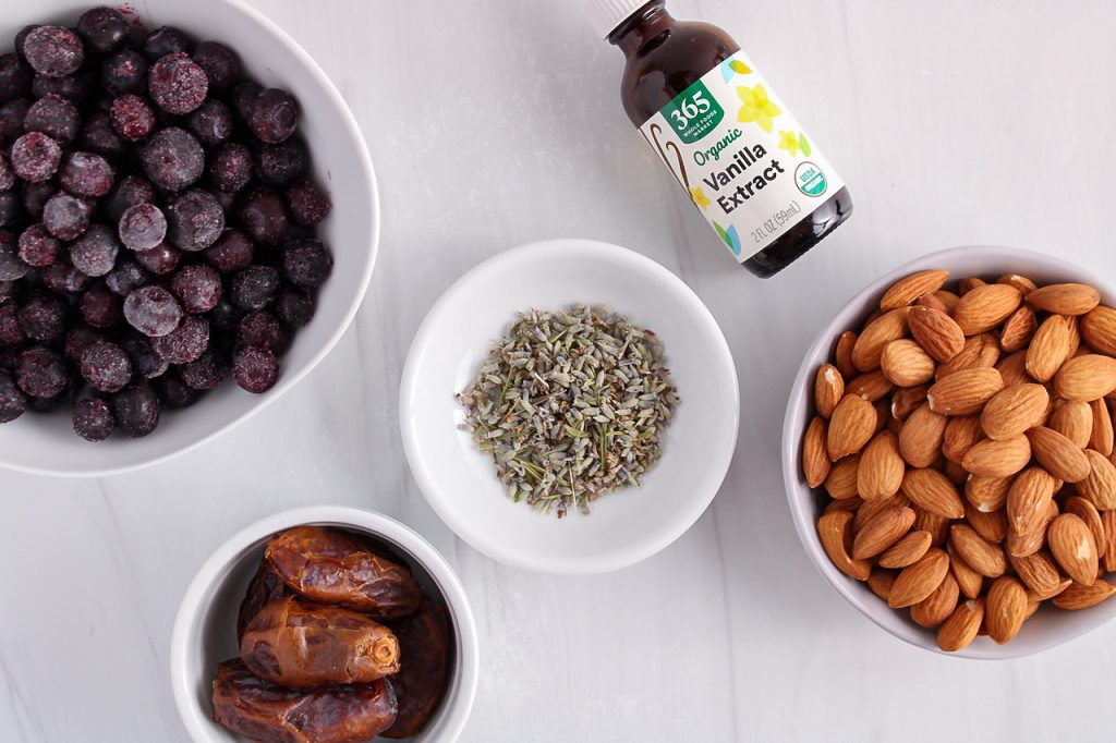 Showing are the ingredients needed to make this recipe: nuts, fruits, vanilla extract, dates and herbs.