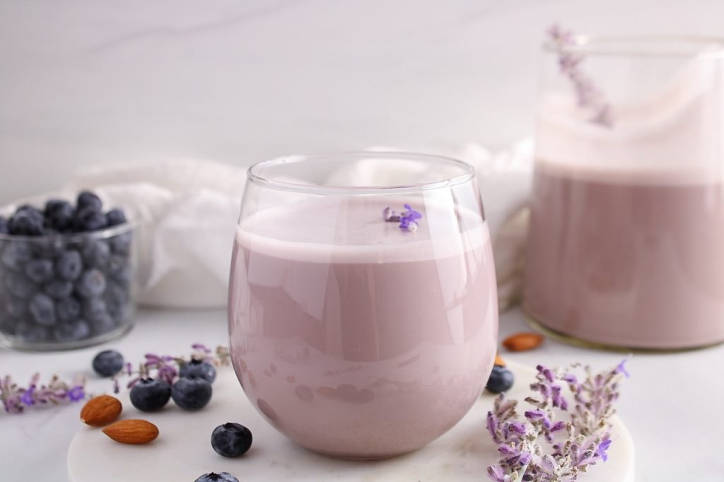 Front view showing a glass on blueberry lavender almond milk. You can see a few lavender flowers floating on top of the milk, more fresh blueberries in the background and a larger jar filled with more of the milk in the background as well.