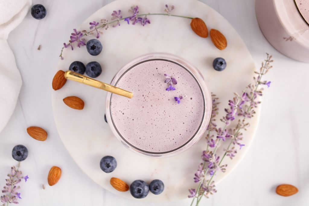 Overhead view on a glass containing a blueberry lavender almond milk. There are lavender flowers floating over the milk and more fresh blueberries, raw almonds and lavender steams on the table around the glass.
