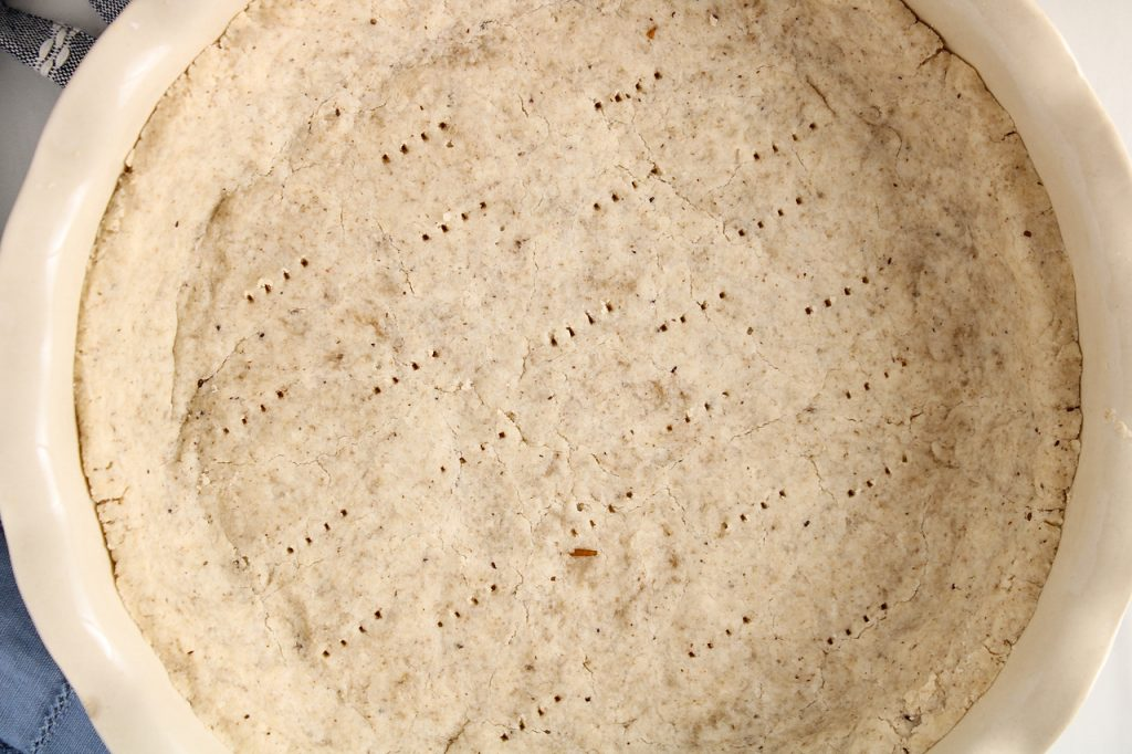 Overhead view on a gluten-free shortcrust pastry that's left empty still in the pie plate. This is a close up picture to show the texture of the crust. There is a dust of ground chia seeds on the side as well.