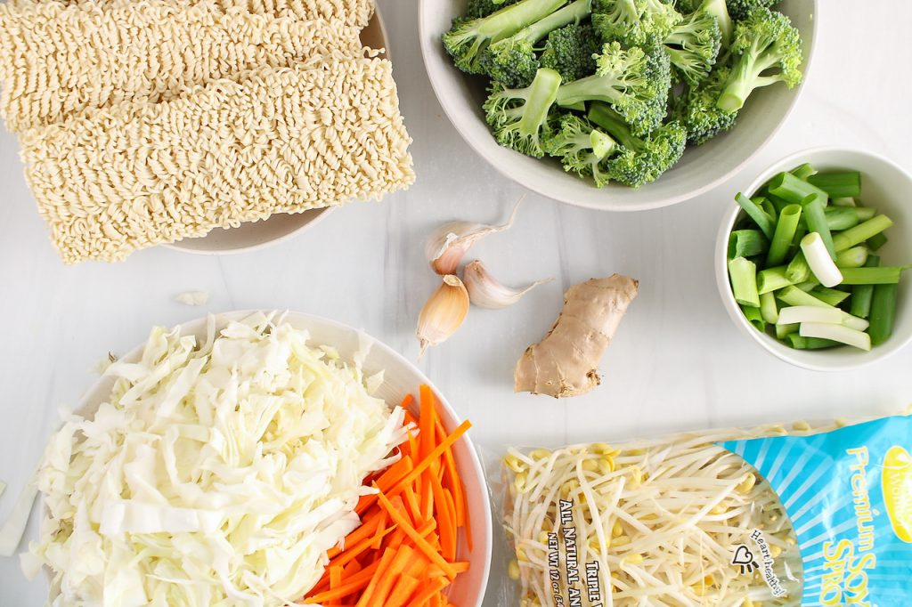 Showing are the ingredients needed to make this recipe: raw noodles, vegetables, garlic, ginger and bean sprout.