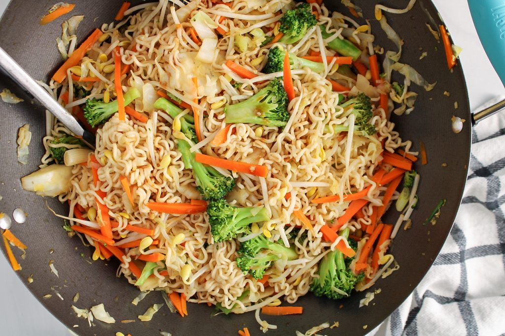Overhead view on a large wok containing Asian style noodles filled with broccoli, carrots and bean sprouts.
