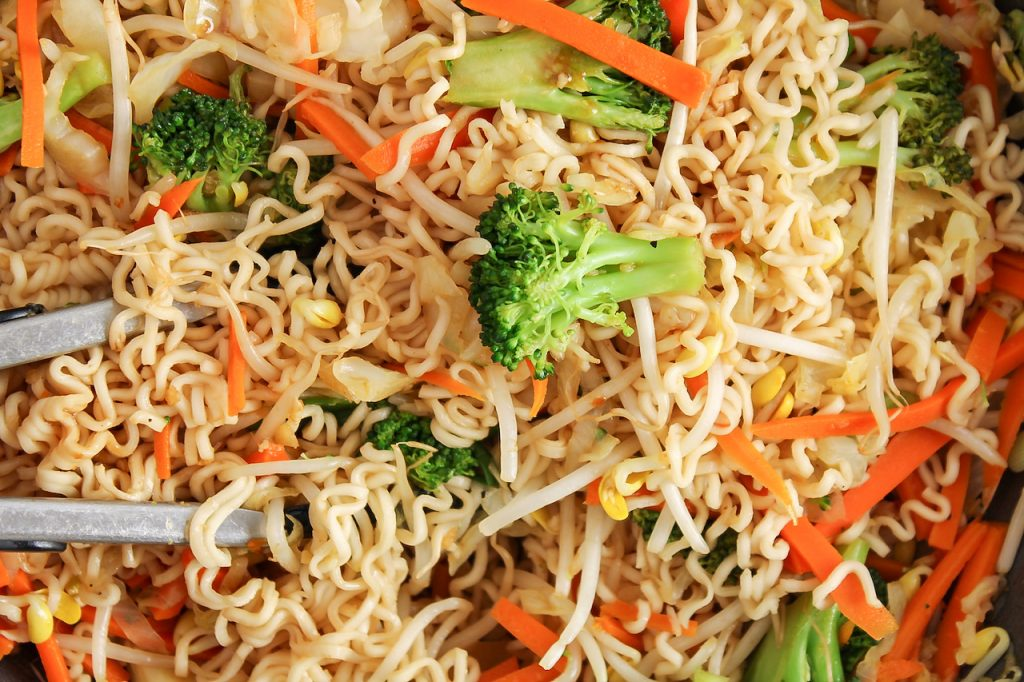 Close up on a large wok containing Asian style noodles filled with broccoli, carrots and bean sprouts. There are thongs in the wok to stir in.