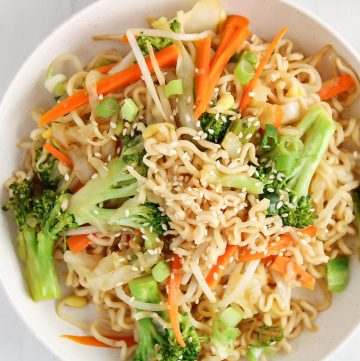 Overhead view on a white bowl containing a vegan chow mein recipe. You can see a close up on the noodles, broccoli, carrots and bean sprouts and there is a garnished of sesame seeds over the bowl.