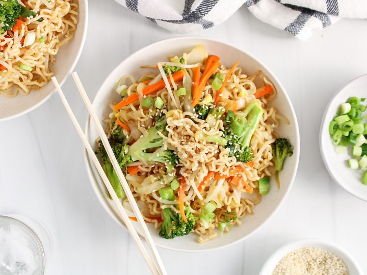 Overhead view on a white bowl containing a vegan chow mein recipe. You can see a close up on the noodles, broccoli, carrots and bean sprouts and there is a garnished of sesame seeds over the bowl. There is a second bowl with more of the noodles and small bowls with sliced green onion and sesame seeds.