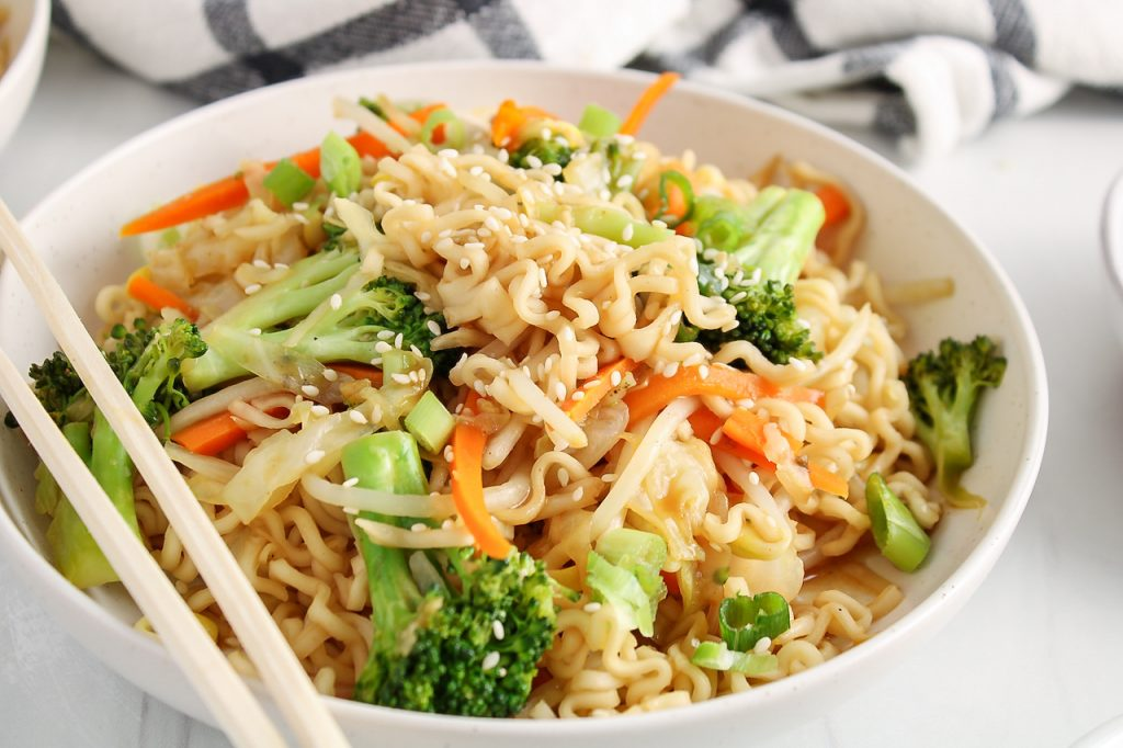 Close up front angle view on a bowl filled with a vegan chow mein. There is a focus on the noodles and you can see chop sticks on the side of the bowl as well.