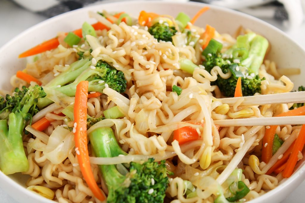 Close up front angle view on a bowl filled with a vegan chow mein. There is a focus on the noodles and you can see chop sticks taking some of the noodles as well.