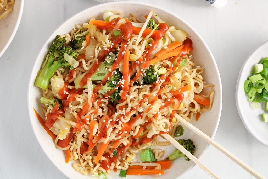 Overhead view on a bowl filled with vegan chow mein. The noodle dish was drizzled with sriracha sauce and there are chopsticks poking in the noodles as well.
