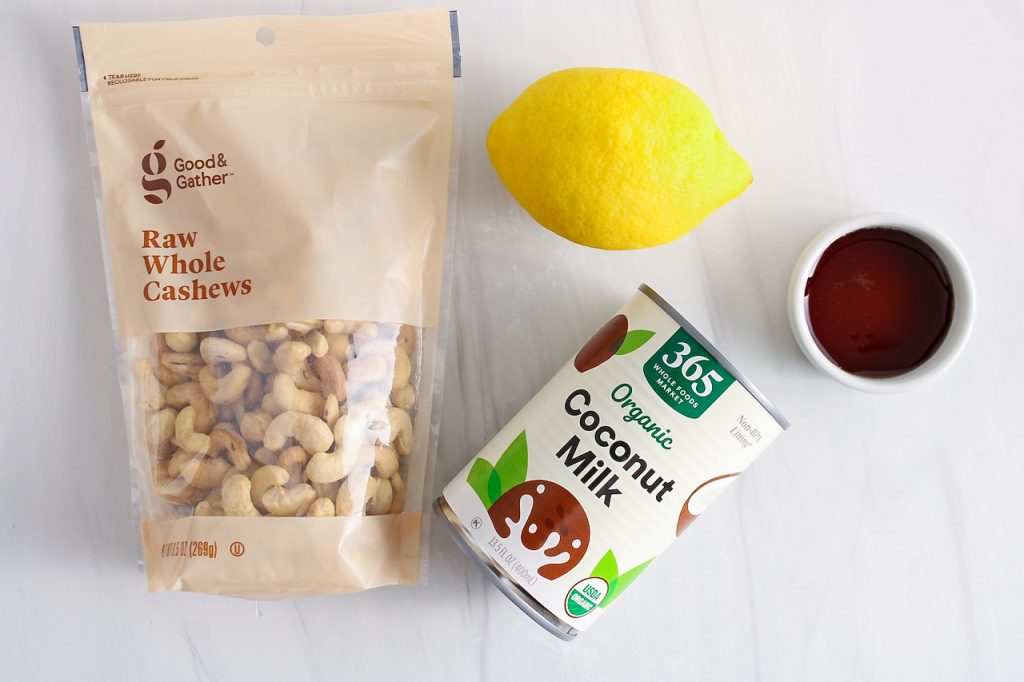 Showing are the ingredients needed to make this recipe: raw cashews, coconut milk, lemon and maple syrup.